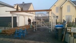Grundkonstruktion des Carports, erste Dachbalken werden angebracht.