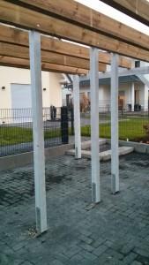 Carport-Grundkonstruktion mit aufgestellten Stützbalken in H-Ankern.